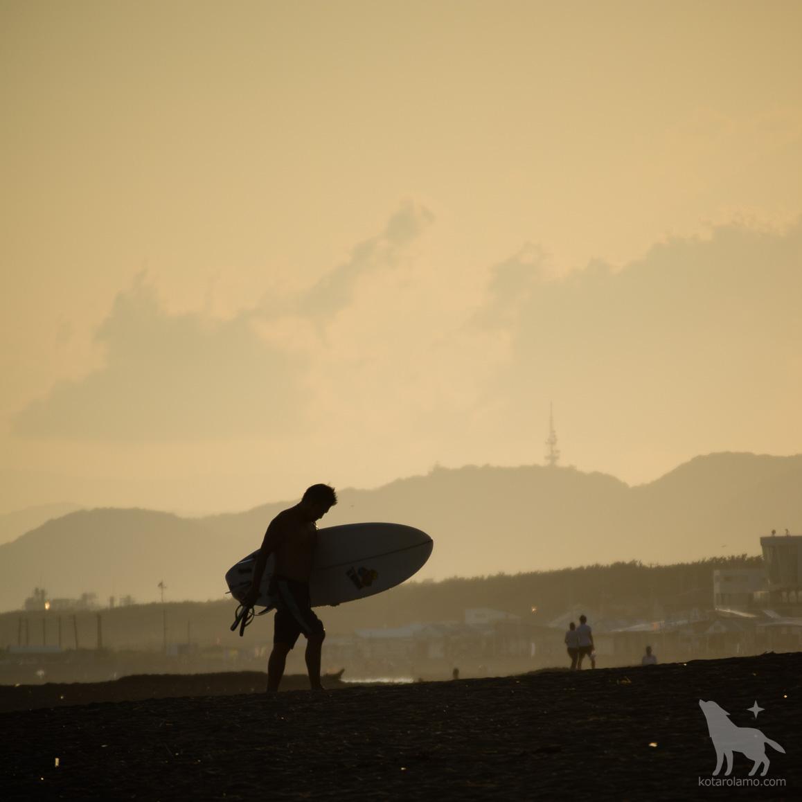 夕暮れ時の浜を歩くサーファー