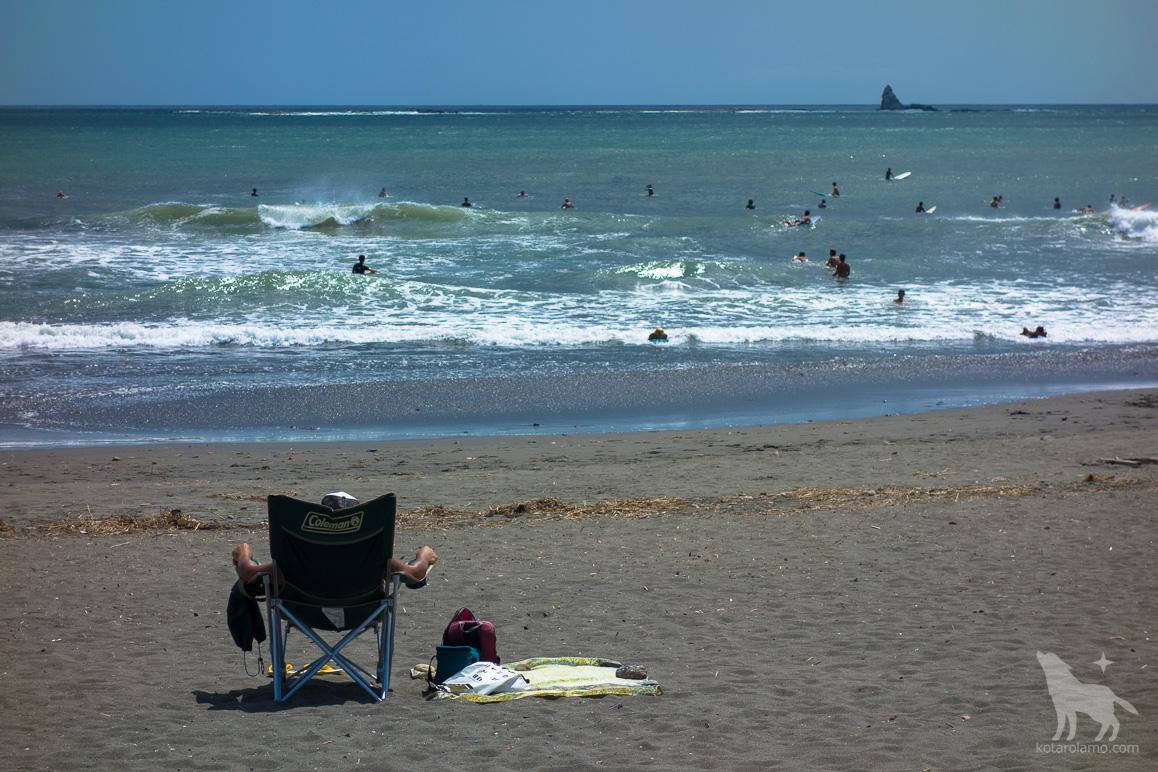 浜でくつろぐ人と烏帽子岩